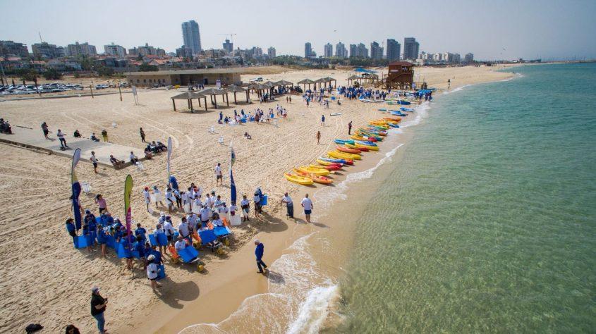 גולשים יוצרים את דגל ישראל בחוף אורנים באשדוד. צילום רחפן: שבתאי טל