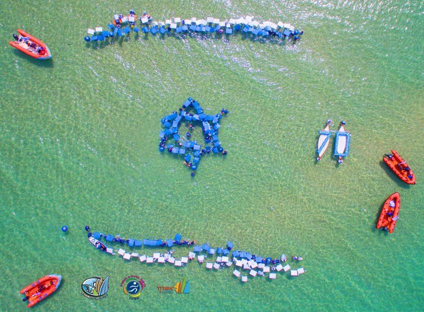 בסימן 70 להקמת המדינה, גולשי אשדוד מציגים: דגל המדינה בים. צילום רחפן: שבתאי טל