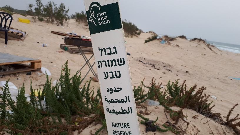 אשפה שהשאירו בליינים על חוף הים בגבול שבין אשדוד לשמורת הטבע ניצנים. צילום: דור גפני