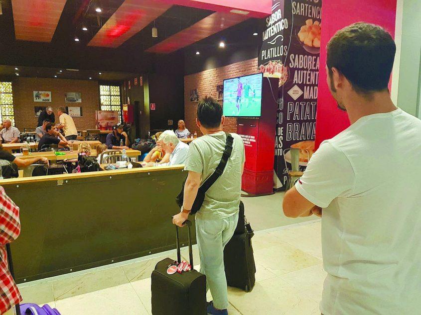 """הבנזוג שי (מימין) מוצא זמן לצפות במשחק בשדה תעופה בחופשה הזוגית בחו""""ל"""