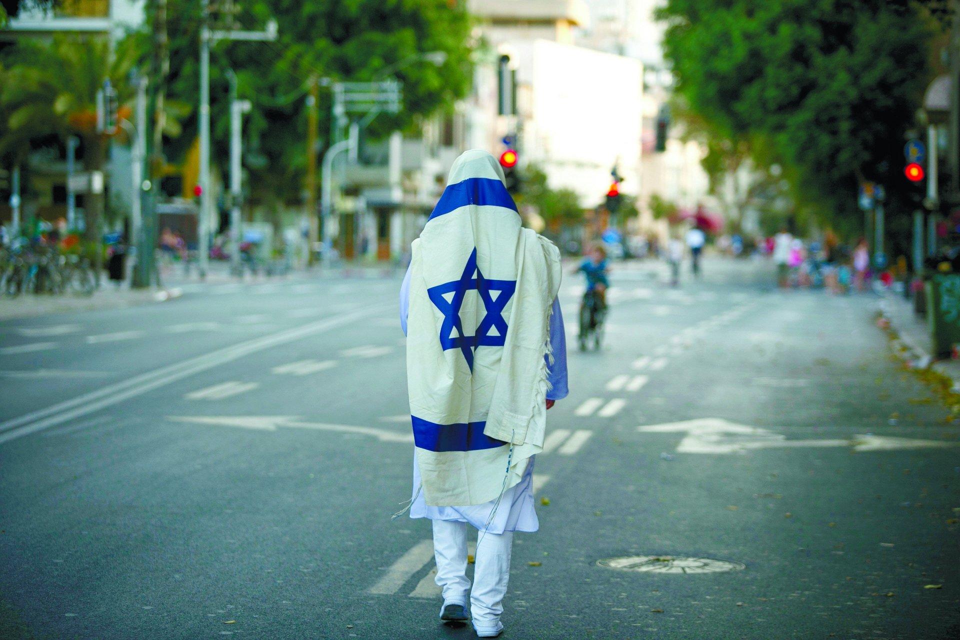 יום כיפור: אחד עם טלית בדרך לבית הכנסת ואחרים על אופניים. צילום: עופר וקנין