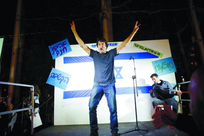 רן כרמי ראש התנועה לשחרור אזריה התפרץ לבמה ערב אחדות בכיכר רבין שארגן סרן זיו שילון שנפצע בעזה. צילום: תומר אפלבאום