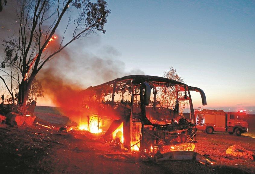 אוטובוס החיילים עולה באש לאחר פגיעת טיל הקורנט. צילום: Menahem KAHANA - AFP