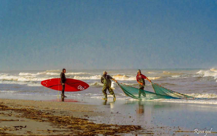 אנשי הים, גולשים ודייגים, נפגשים במוצא נחל לכיש, לאחר שוך הגשמים. צילום: רינה גל