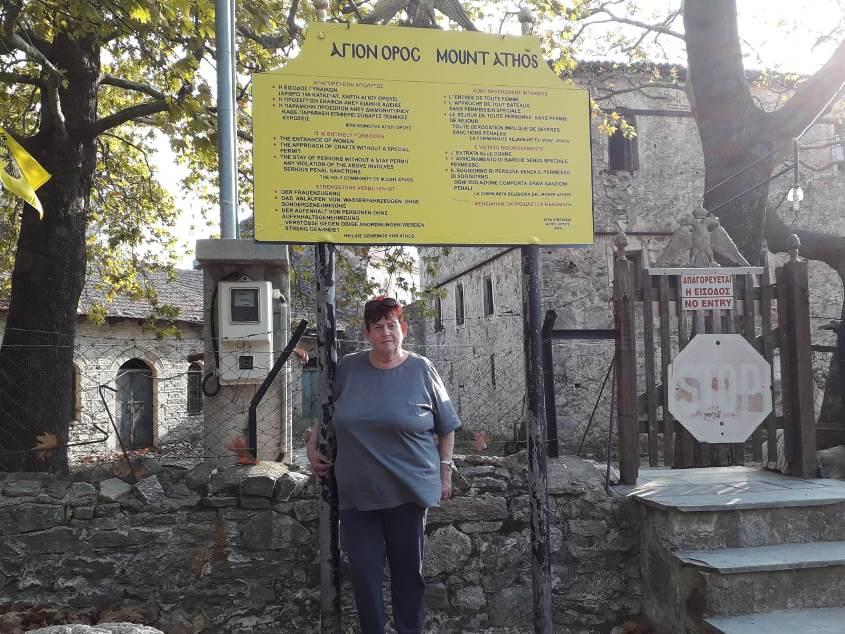 רבקה יניב בכניסה היבשתית לאתוס, ארץ המנזרים האוטונומית, מעליה השלט האוסר כניסה לנשים בשפות שונות. צילום: איציק יניב