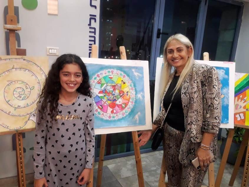 אושר כהן ומנהלת בית הספר נוף-ים עליזה יפרח ליד הציור הזוכה. צילום: אורטל כהן