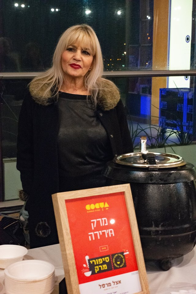 מרסל נוימן עם מרק החרירה שהכינה בערב הגאלה בבית קלנג שפתח את פסטיבל סיפורי מרק באשדוד. צילום: אסף מיימון