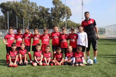 יאיר אזולאי וילדי בית הספר לכדורגל של האדומים. צילום: מיכאל בן עזרא.