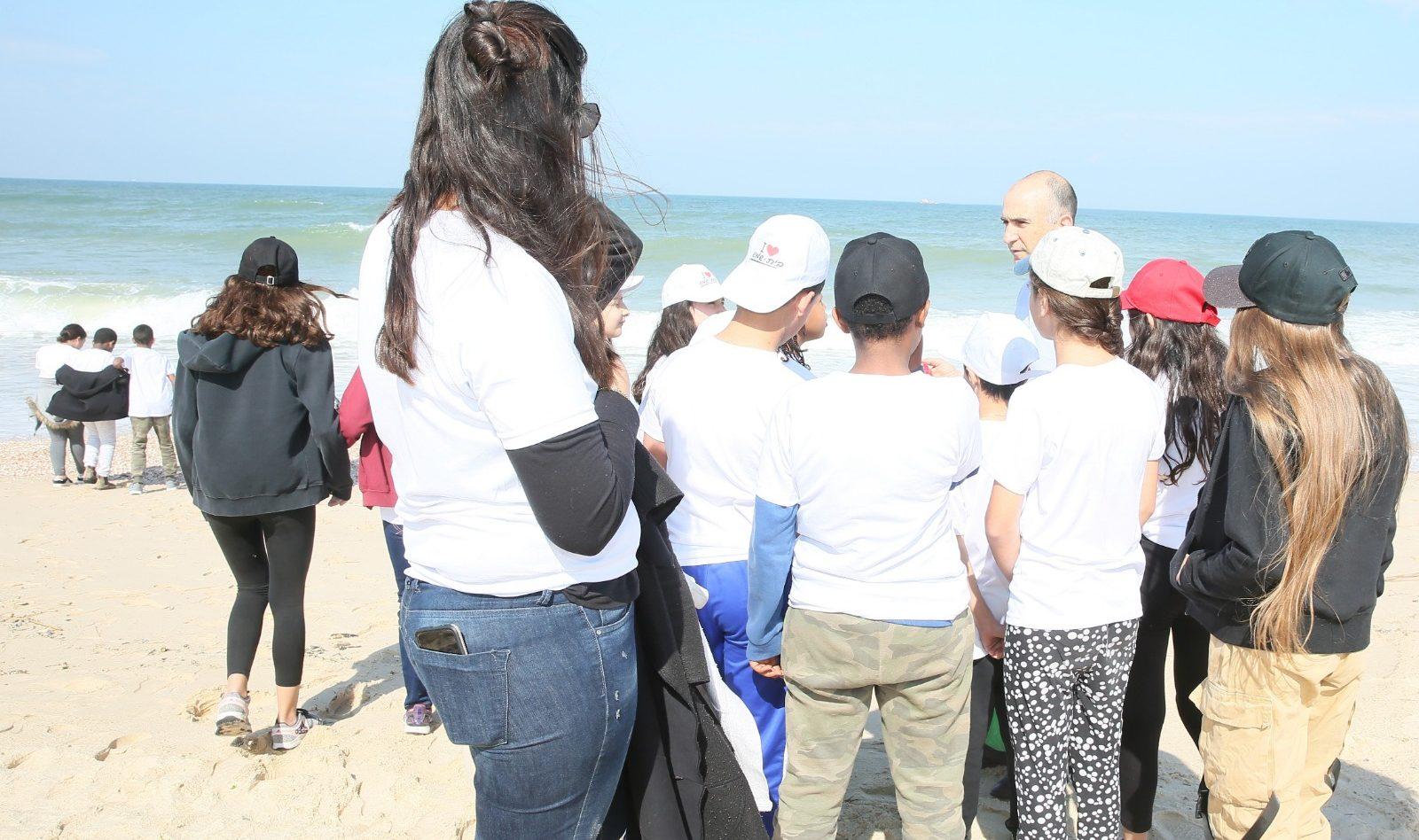"""מנכ""""ל המשרד להגנת הסביבה גיא סמט עם תלמידי ביה""""ס ז'בוטינסקי מבית שמש בחוף ניצנים. צילום: מירי שמעונוביץ לעמ"""