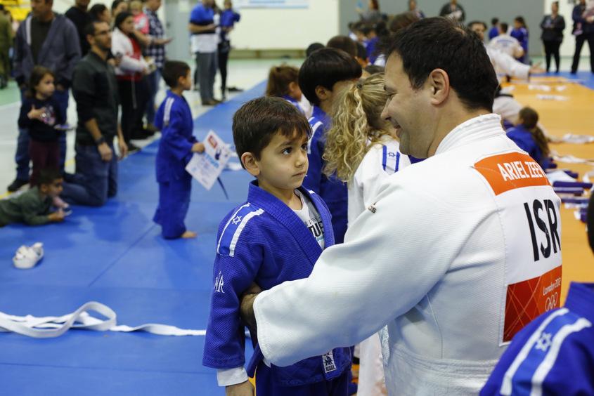 אריק זאבי מעניק חגורה לג'ודוקא צעיר. צילום: פבל