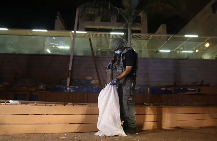 חבלן של המשטרה אוסף את שרידי הרקטה. צילום: אילן אסייג