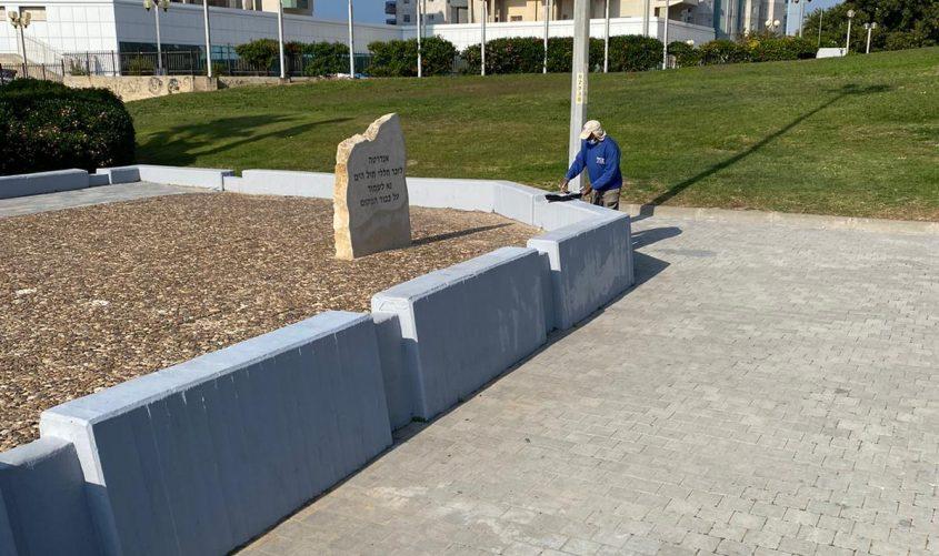 עובד עירייה מנקה את האנדרטה
