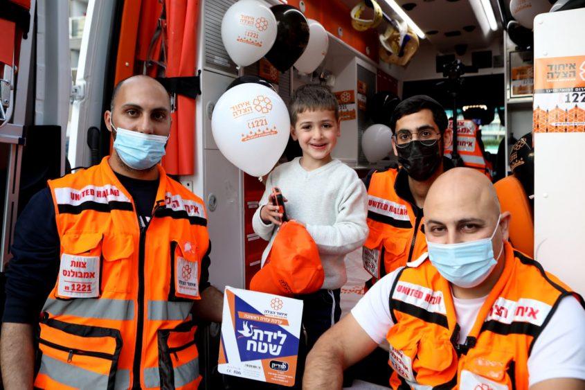 המתנדבים חוגגים באמבולנס עם התאומים. צילום: דוברות איחוד הצלה