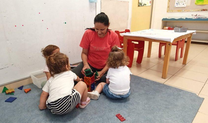 כלנית אבידן סייעת בכיתת תינוקייה במעון החורש מדריכה מיומנויות משחק ומוטוריקה. צילום: דודו בן זינו